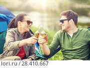 Купить «happy couple clinking drinks at campsite tent», фото № 28410667, снято 27 мая 2016 г. (c) Syda Productions / Фотобанк Лори