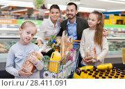 Купить «Family is standing with cart with products in the supermarket.», фото № 28411091, снято 4 апреля 2018 г. (c) Яков Филимонов / Фотобанк Лори