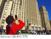 Купить «Турист фотографирует на смартфон здание МИД России. Москва», фото № 28411775, снято 10 мая 2018 г. (c) Oles Kolodyazhnyy / Фотобанк Лори