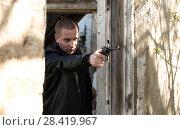 Купить «man is aiming with a pistol», фото № 28419967, снято 1 мая 2018 г. (c) Александр Лычагин / Фотобанк Лори