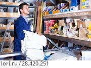 Купить «Sellerman in uniform is putting bags on the shelves in the building store.», фото № 28420251, снято 26 июля 2017 г. (c) Яков Филимонов / Фотобанк Лори