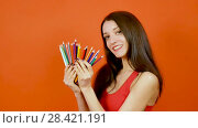 Купить «Smiling Attractive Girl Holding a Set of Colorful Pencils in Her Hands and Posing in Studio on an Orange Background. Art Design Concept», видеоролик № 28421191, снято 19 апреля 2018 г. (c) Ольга Балынская / Фотобанк Лори