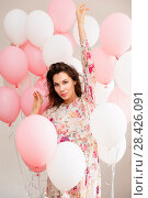 Купить «Beautiful young girl in dress with balloons on birthday. Portrait of cute woman with multicolored balloon. Cute brunette girl in the studio with balls filled», фото № 28426091, снято 29 апреля 2018 г. (c) Сергей Тимофеев / Фотобанк Лори