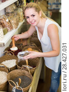 Купить «Smiling woman buying dried beans by weight», фото № 28427031, снято 15 ноября 2018 г. (c) Яков Филимонов / Фотобанк Лори