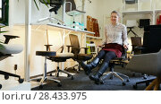 Купить «Portrait of happy girl sitting in comfortable office chair bought in furnishings store», видеоролик № 28433975, снято 28 марта 2018 г. (c) Яков Филимонов / Фотобанк Лори