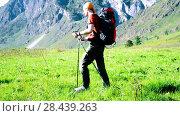 Купить «Hiking man walking on green mountain meadow with backpack. Summer sport and recreation concept.», видеоролик № 28439263, снято 17 апреля 2018 г. (c) Александр Маркин / Фотобанк Лори