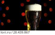 Купить «A glass of cold beer on a black background with colored lights. Drops of water flow down the glass. HD», видеоролик № 28439867, снято 20 мая 2018 г. (c) Поцелуев Константин Валерьевич / Фотобанк Лори