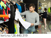 Купить «Ordinary man choosing sport shirt in shop», фото № 28440319, снято 8 января 2018 г. (c) Яков Филимонов / Фотобанк Лори