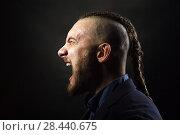 Купить «man with dreadlocks screams in a rage, looks like a viking, Iroquois haircut», фото № 28440675, снято 1 февраля 2018 г. (c) Restyler Viacheslav / Фотобанк Лори
