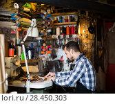Купить «male worker sewing stitches on belt in leather workshop», фото № 28450303, снято 22 марта 2019 г. (c) Яков Филимонов / Фотобанк Лори