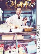 Купить «Seller offering displayed sorts of meat», фото № 28450635, снято 2 января 2017 г. (c) Яков Филимонов / Фотобанк Лори
