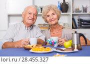 Купить «Smiling elderly spouses enjoying tea with sweets», фото № 28455327, снято 28 августа 2017 г. (c) Яков Филимонов / Фотобанк Лори