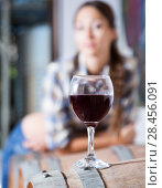 girl looking at glass of red wine standing on wooden barrel in winery. Стоковое фото, фотограф Татьяна Яцевич / Фотобанк Лори