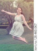 Купить «young brunette woman in dress jumping at the outdoors», фото № 28460067, снято 18 апреля 2017 г. (c) Яков Филимонов / Фотобанк Лори