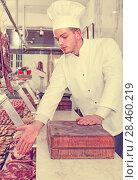 Купить «Professional cook sniffing freshly cooked dish», фото № 28460219, снято 20 июля 2018 г. (c) Яков Филимонов / Фотобанк Лори