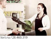 Купить «Smiling woman seller helping customer to weigh cabbage», фото № 28460319, снято 23 ноября 2016 г. (c) Яков Филимонов / Фотобанк Лори