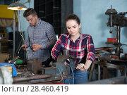 Купить «Portrait of adult female working near vise», фото № 28460419, снято 10 октября 2017 г. (c) Яков Филимонов / Фотобанк Лори