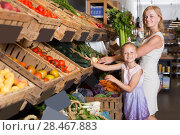 Купить «Portrait of woman and girl buying greens», фото № 28467883, снято 6 июня 2020 г. (c) Яков Филимонов / Фотобанк Лори