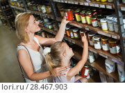 Купить «Portrait of woman and girl buying conserve tomato sauce», фото № 28467903, снято 17 октября 2018 г. (c) Яков Филимонов / Фотобанк Лори