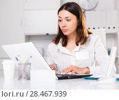 Купить «Upset woman working with laptop and papers at the office», фото № 28467939, снято 1 мая 2018 г. (c) Яков Филимонов / Фотобанк Лори