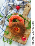 Bagel with cumin, arugula, radish and smoked trout. Стоковое фото, фотограф Марина Сапрунова / Фотобанк Лори