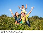 Купить «Positive family of three people outdoors», фото № 28469459, снято 12 декабря 2018 г. (c) Светлана Кузнецова / Фотобанк Лори