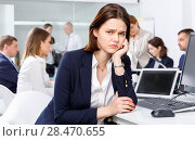 Купить «Portrait of unhappy girl in modern open plan office on background with coworkers», фото № 28470655, снято 21 апреля 2018 г. (c) Яков Филимонов / Фотобанк Лори