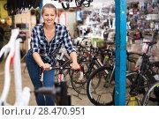 Купить «Portrait of girl who is standing with bicycle in store.», фото № 28470951, снято 13 сентября 2017 г. (c) Яков Филимонов / Фотобанк Лори