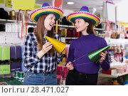 Купить «Attractive girls trying on party hats in festive accessories store», фото № 28471027, снято 15 марта 2018 г. (c) Яков Филимонов / Фотобанк Лори