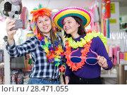 Купить «Girls taking selfie in store of festival accessories», фото № 28471055, снято 15 марта 2018 г. (c) Яков Филимонов / Фотобанк Лори