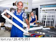 Купить «Craftsman in workwear is standing with window frame from pvc pro», фото № 28475951, снято 19 июля 2017 г. (c) Яков Филимонов / Фотобанк Лори