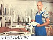 Focused workman in overalls controlling quality of assembly of p. Стоковое фото, фотограф Яков Филимонов / Фотобанк Лори
