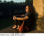 Woman leaning against wall of temple, Krong Siem Reap, Siem Reap, Cambodia. Стоковое фото, фотограф Keith Levit / Ingram Publishing / Фотобанк Лори