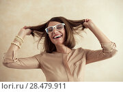 Купить «Happy excited woman dancing cheerful with wind in the hair on beige background», фото № 28479911, снято 18 января 2014 г. (c) Ingram Publishing / Фотобанк Лори