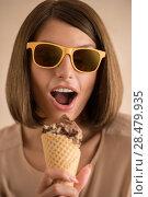 Купить «Ice cream woman singing in cone like in microphone happy, joyful and cheerful. Cute young female model eating ice cream cone», фото № 28479935, снято 18 января 2014 г. (c) Ingram Publishing / Фотобанк Лори