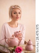 Young beautiful woman having tea-party in pink feminine style. She is very satisfacted. Valentine's day or international women's day celebration. Стоковое фото, фотограф Kirill Kedrinskiy / Ingram Publishing / Фотобанк Лори