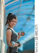 Купить «Athletic woman pumping up muscles with dumbbells outdoors in the city», фото № 28480571, снято 22 июня 2014 г. (c) Ingram Publishing / Фотобанк Лори