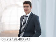 Portrait of handsome confident young businessman standing arms in pockets, smiling happy, looking at camera. Стоковое фото, фотограф Kirill Kedrinskiy / Ingram Publishing / Фотобанк Лори