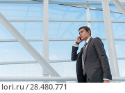 Купить «Man on smart phone - young business man in airport. Casual urban professional businessman using smartphone smiling happy inside office building or airport. Handsome man wearing suit jacket indoors.», фото № 28480771, снято 20 июля 2014 г. (c) Ingram Publishing / Фотобанк Лори