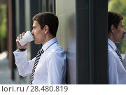 Купить «Businessman drinking coffee leaning on wall of modern office building. Urban professional smiling happy wearing white shirt holding disposable coffee cup. Handsome male model in his twenties.», фото № 28480819, снято 20 июля 2014 г. (c) Ingram Publishing / Фотобанк Лори