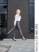 Купить «Business woman walking with suitcase near modern office building or hotel», фото № 28480983, снято 20 июля 2014 г. (c) Ingram Publishing / Фотобанк Лори