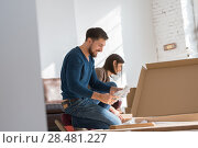 Купить «Happy young couple putting together self assembly furniture as they move into their new house», фото № 28481227, снято 10 октября 2014 г. (c) Ingram Publishing / Фотобанк Лори