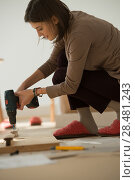 Купить «Woman Putting Together Self Assembly Furniture In New Home», фото № 28481243, снято 10 октября 2014 г. (c) Ingram Publishing / Фотобанк Лори