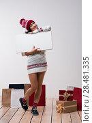 Купить «Christmas woman hold big white card copyspace. Winter knitted beanie hat. Full length.», фото № 28481335, снято 15 октября 2014 г. (c) Ingram Publishing / Фотобанк Лори