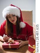 Купить «Young pretty woman wearing Santa Claus hat wrapping Christmas gift at her desk», фото № 28481635, снято 12 ноября 2014 г. (c) Ingram Publishing / Фотобанк Лори