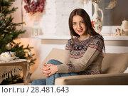 Купить «Beautiful woman wearing winter outfit sitting on couch at home near Christmas tree», фото № 28481643, снято 12 ноября 2014 г. (c) Ingram Publishing / Фотобанк Лори