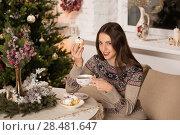 Купить «Beautiful woman wearing winter outfit drinking tea with candy at home near Christmas tree», фото № 28481647, снято 12 ноября 2014 г. (c) Ingram Publishing / Фотобанк Лори