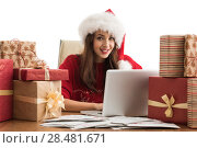 Купить «Young pretty woman wearing Santa Claus hat wrapping Christmas gift at her desk and responding to children messages and wishes by email», фото № 28481671, снято 12 ноября 2014 г. (c) Ingram Publishing / Фотобанк Лори