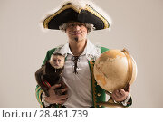 Mature man adventurer in costume of traveler with his monkey companion and vintage globus on gray background. Стоковое фото, агентство Ingram Publishing / Фотобанк Лори