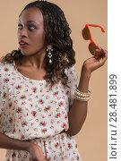Купить «Portrait of cute african woman posing - holding sunglasses and looking away», фото № 28481899, снято 19 ноября 2014 г. (c) Ingram Publishing / Фотобанк Лори